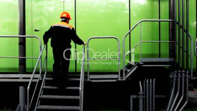 Worker Climbs Stairs And Goes By Ladder