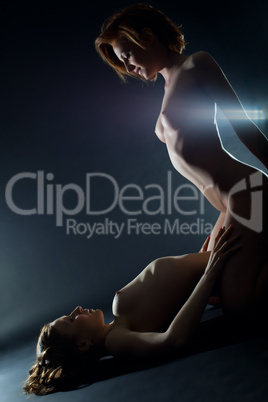 Two naked playful lesbian woman in dark