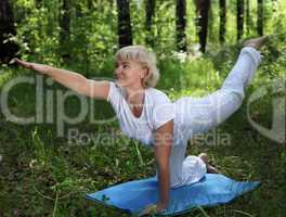 An elderly woman practices yoga
