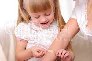 little girl puts a plaster