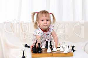 Little girl playing chess