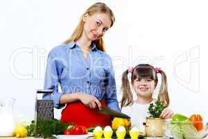 Young mother cooking at home with her daoghter