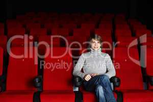 Young man sitting in the cinema alone
