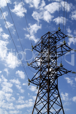Power transmission line against blue sky with clouds