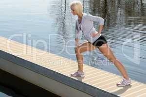Sport woman stretch body on lake pier