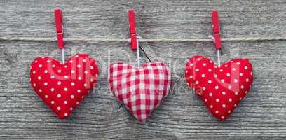 Drei rote Herzen auf Holzbrett