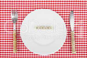 White plate with Hungry-lettering and cutlery