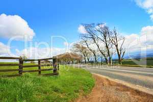 Rural road, wooden fence and blue sky