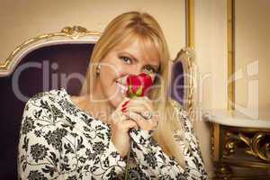 Seated Woman Smiling While Smelling Red Rose