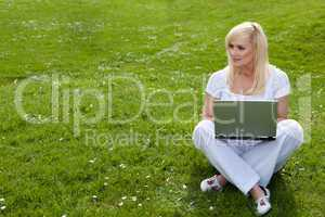 Woman with laptop on green lawn