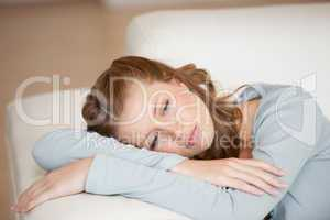 Woman lying on a sofa crossing her arms looking down