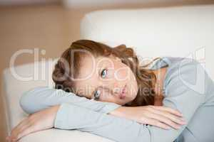 Woman crossing harms while lying on a sofa looking up