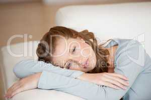 Woman lying on a sofa crossing her arms