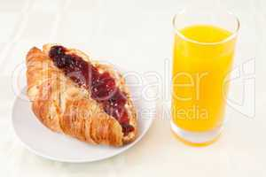 Croissant next to a glass of orange juice
