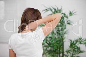 Brunette massaging her painful neck