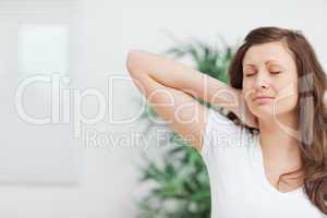 Woman placing her hand on her painful neck