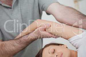 Osteopath holding the arm of a woman while massaging her body
