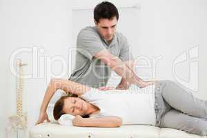 Osteopath crossing his arms while massaging a woman