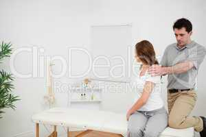 Osteopath looking at the back of a woman