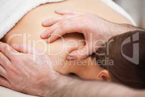 Osteopath massaging his patient while pressing his tumb