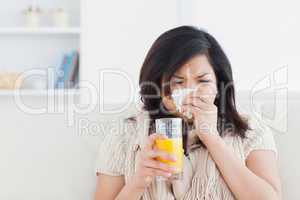 Sneezing woman drinking a glass of orange juice