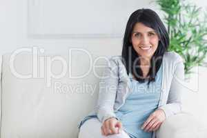 Smiling woman sitting at the end of a couch