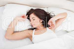 Peaceful woman stretching her body while getting up