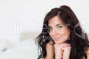 Smiling woman lying on her white duvet