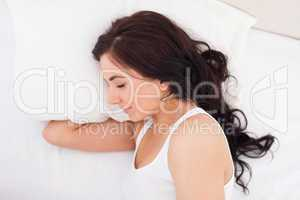 Brunette woman lying on the side while sleeping