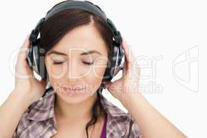 Brunette with headphones closing her eyes