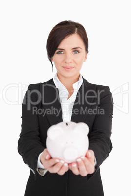 Beautiful businesswoman holding a piggy-bank