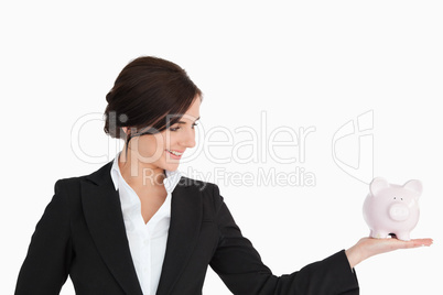 Businesswoman with a piggy-bank on her palm