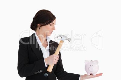 Businesswoman going to break a piggy-bank