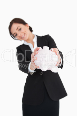 Businesswoman emptying a piggy-bank