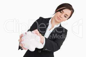 Young woman in suit emptying a piggy bank