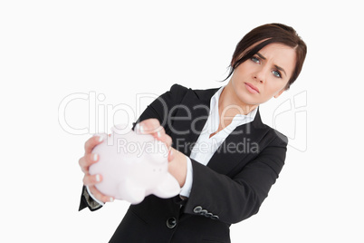 Upset businesswoman holding an empty piggy bank