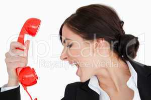 Woman in suit shouting against a red dial telephone