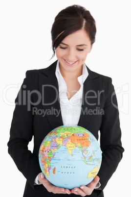 Brunette woman in suit holding an earth globe