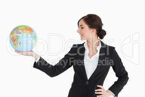 Brunette businesswoman holding an earth globe in her palm