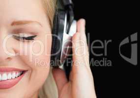 Joyful woman closing her eyes while listening to music