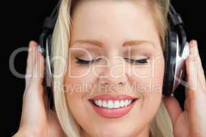 Cheerful woman closing her eyes while listening to music