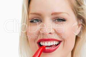 Blonde woman biting a chili