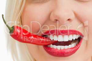 Smiling woman holding a chili with her teeth