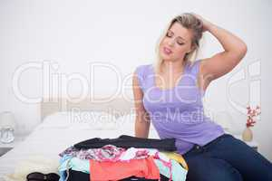 Blonde rubbing her head while looking at her full suitcase