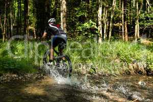 Mountainbiker fährt duch einen Bach