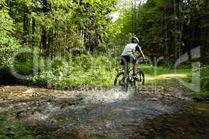 Mountainbiker durchquert Bach