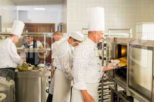 Group of cooks in professional kitchen