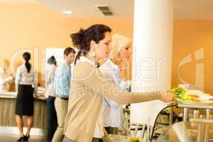 Young business colleagues select canteen lunch