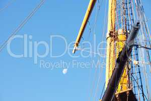 mast ship and the moon against the blue sky