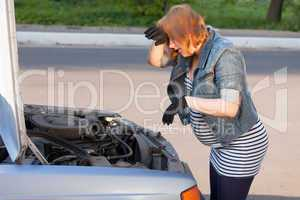 Pregnant Woman Trying to Repair the Car